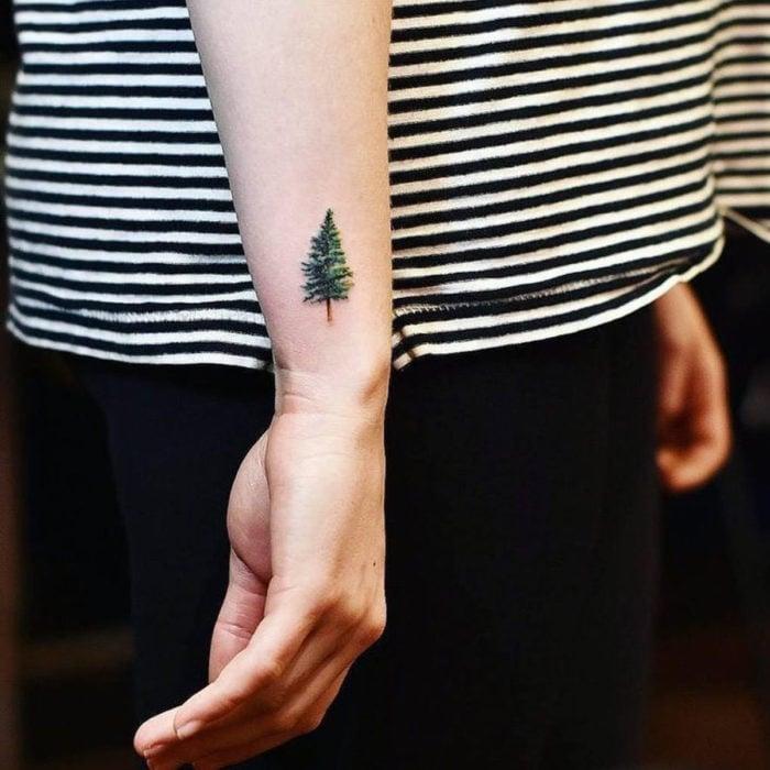 Tatuajes pequeños en la muñeca; árbol pino