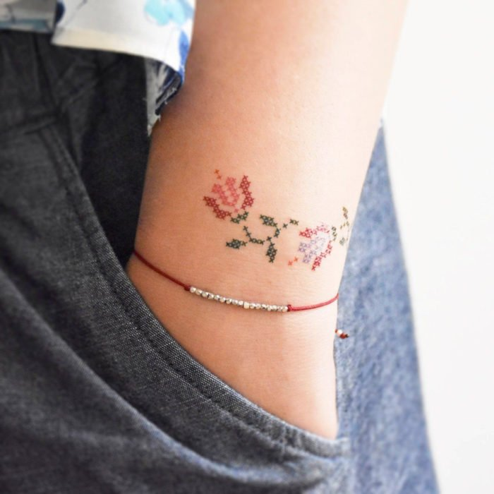 Tatuajes pequeños en la muñeca; flores tejidas