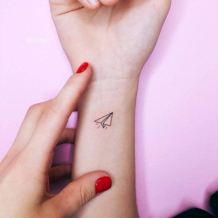 Tatuajes pequeños en la muñeca; avión de papel