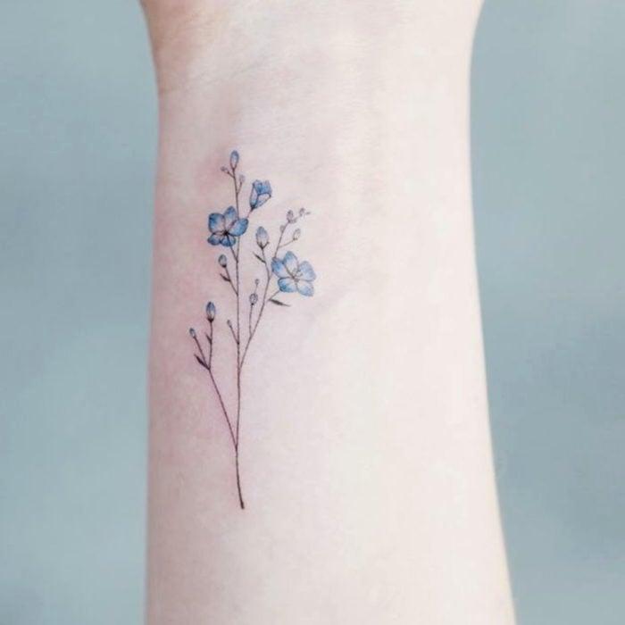 Tatuajes pequeños en la muñeca; flores azules