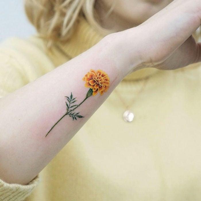 Tatuajes temporales; flor de cempasúchil en el brazo