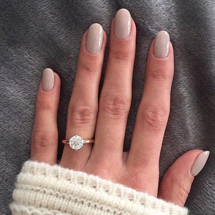 Chica con las uñas pintadas en color piel y de forma redondeada