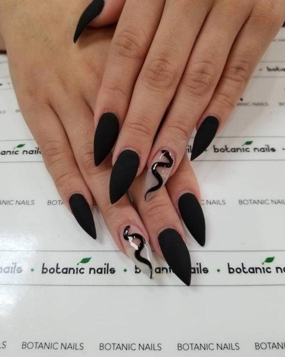 Uñas de tipo stiletto en color negro con una vivora