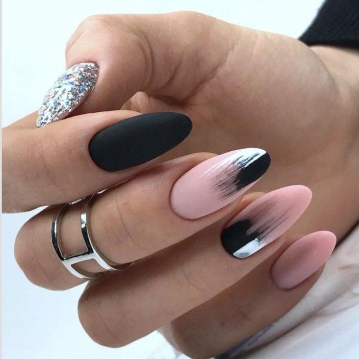 Chica con las uñas en forma de almendra y pintadas en color negro con rosa