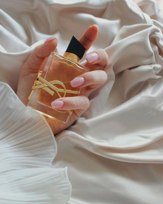 Mano de mujer sostiene botella de perfume en la cama