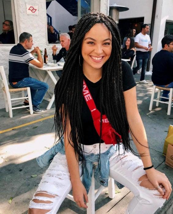 Looks con trenzas africanas; mujer sonriendo sentada en un café, cabello lardo y negro, jeans desgastados
