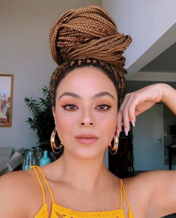 Looks con trenzas africanas; mujer con cabello castaño rubio largo, chongo grueso, maquillaje natural y arracadas