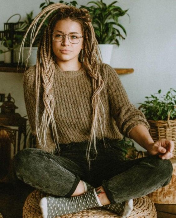 Looks con trenzas africanas; mujer con lentes vintage, suéter tejido café, cabello rubio y largo, sentada en taburete de rafia