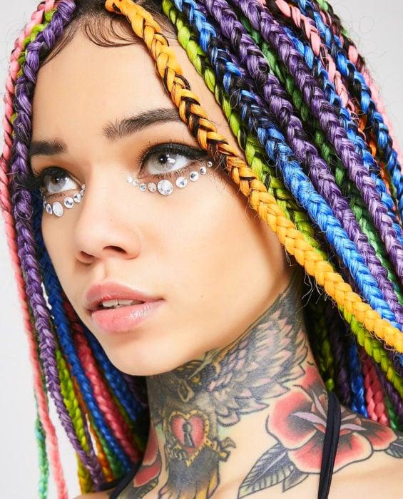 Looks con trenzas africanas; mujer de ojos grises, con cabello de colores arcoíris, anaranjadi, verde, azul, morado y rosa, con tatuaje de búho, rosa y corazón en el cuello, con piedras en los ojos