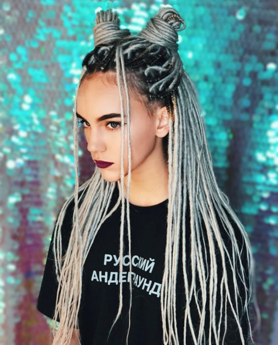 Looks con trenzas africanas; mujer de cabello largo y gris peinado en dos medios chingos altos