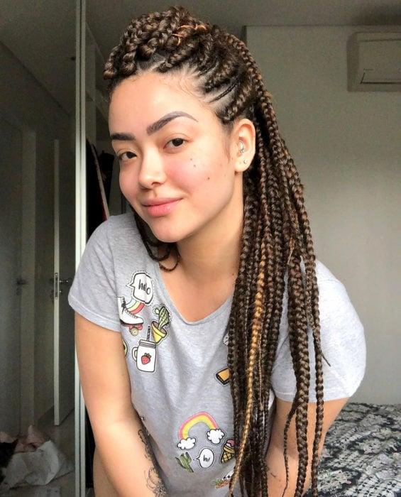 Looks con trenzas africanas; mujer de ojos rasgados, cabello castaño y largo, con lunares