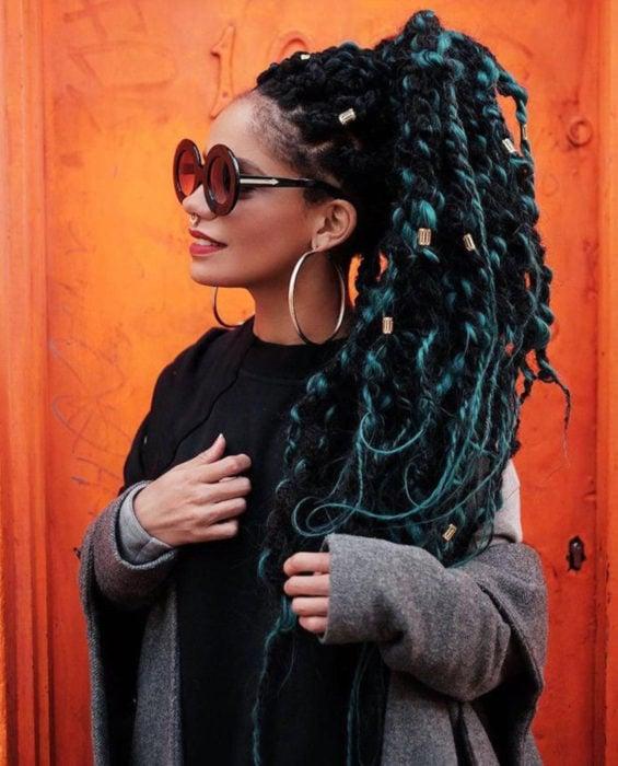 Looks con trenzas africanas; mujer morena con lentes redondos y gruesos, cabello negro y verde largo, peinado en una cola de caballo con accesorios dorados, arracadas grandes y piercing en el tabique