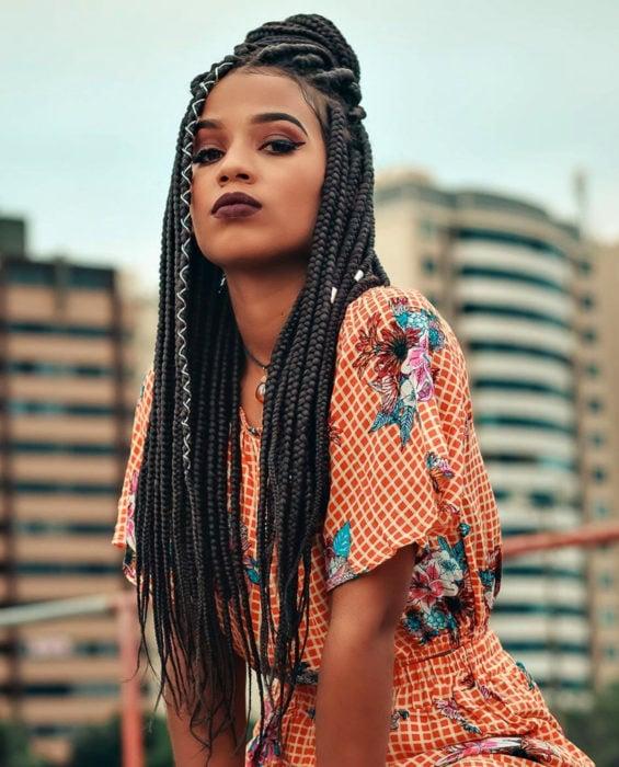 Looks con trenzas africanas; mujer morena de cabello largo y castaño