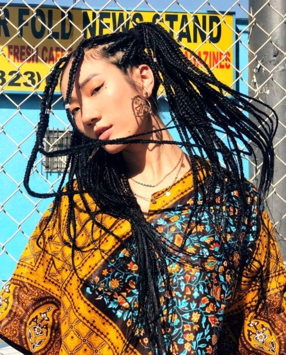 Looks con trenzas africanas; mujer asiática de ojos rasgados con cabello largo y negro, con peinado de coletas y aretes de rosto, ropa hippie