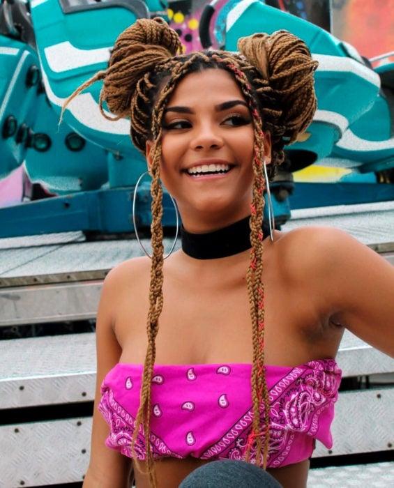 Looks con trenzas africanas; mujer morena sonriendo, con cabello castaño rubio largo, peinado de dos chongos altos, crop top de paliacate rosa y gargantilla negra