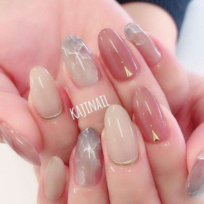 Diseño de manicura en tonos rosa, beige y azul, con detalles dorados