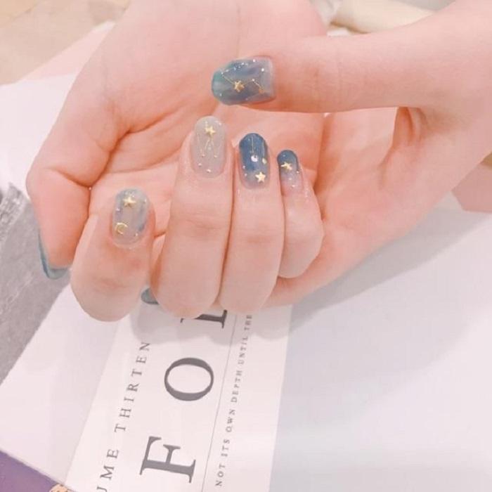 Diseño de manicura en tonalidades azule cielo y detalles dorados