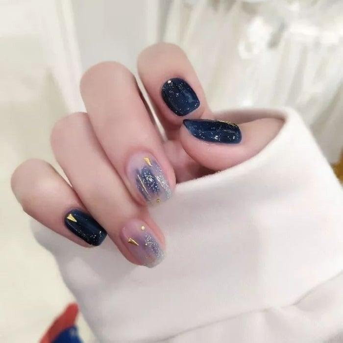 Diseño de manicura en tonalidades azul marino y cielo y detalles dorados