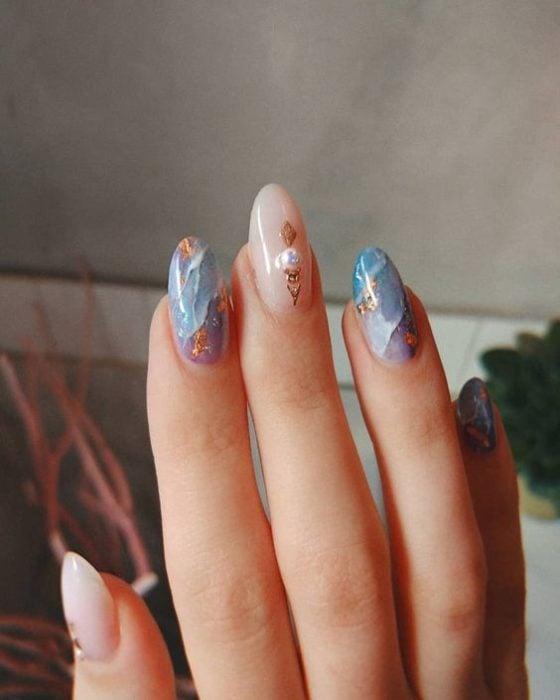 Diseño de manicura en tonos azules y rosas con detalles dorados