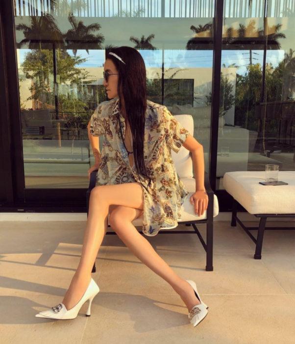 Vera Wang; mujer de cabello castaño, lacio y largo, sentada con vestido y las piernas cruzadas, zapatos stilettos blancos
