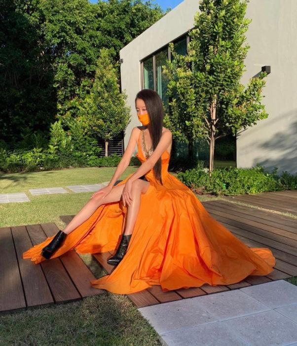 Vera Wang presume abdomen de acero; mujer sentada en el jardín con largo vestido anaranjado de princesa