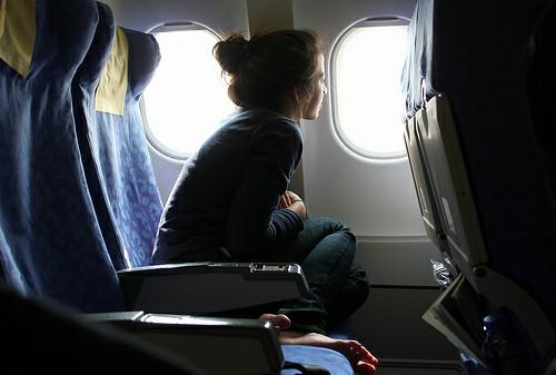 Chica sentada en un avión mirando por la vetana