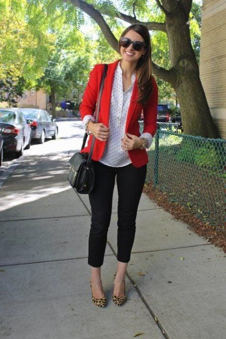 Mujer con saco rojo, pantalón negro y zapatillas en animal print