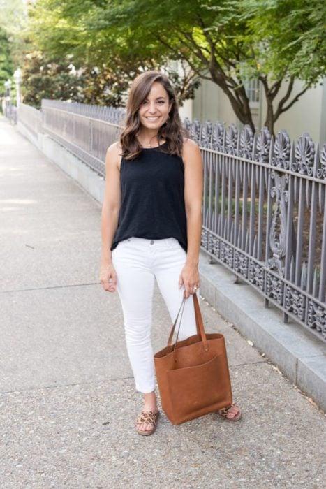Mujer con bolsa grande color café usa blusa negra y pantalón blanco con sandalias animal print