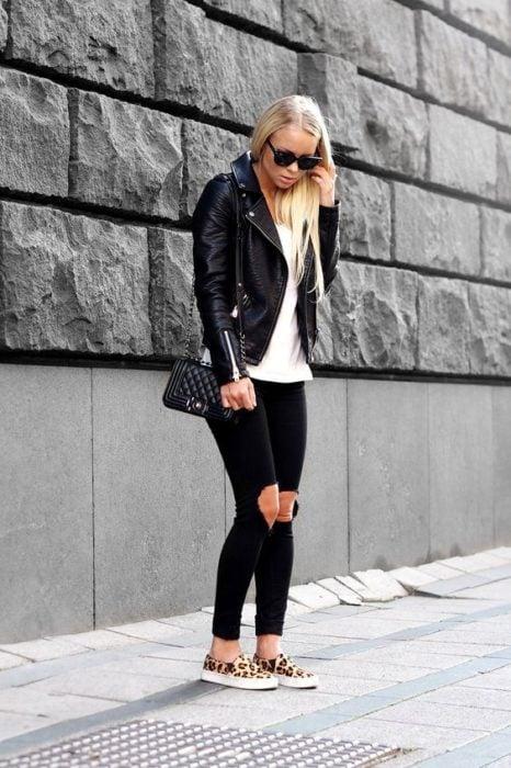 Chica rubia con cabello suelto y outfit negro usa zapatos animal print