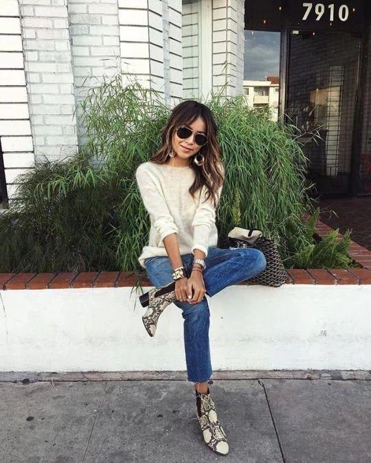 Chica morena con cabello ondulado y lentes oscuros sentada con jeans, blusa blanca y zapatos animal print