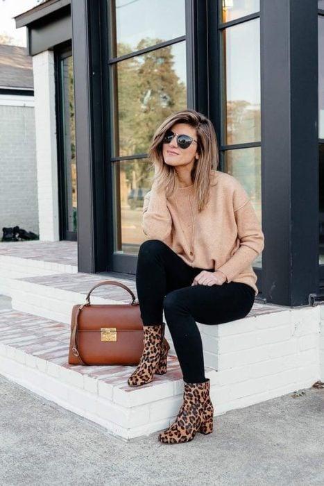Mujer rubia con melena corta sentada con jeans, suéter rosa y botines animal print