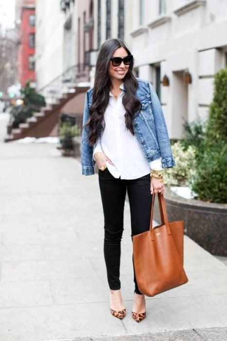 Chica de pelo negro largo posa con pantalón negro, blusa blanca y chamarra de mezclilla