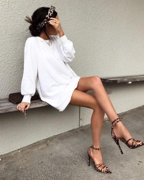 Chica sentada con vestido blanco y tacones de animal print