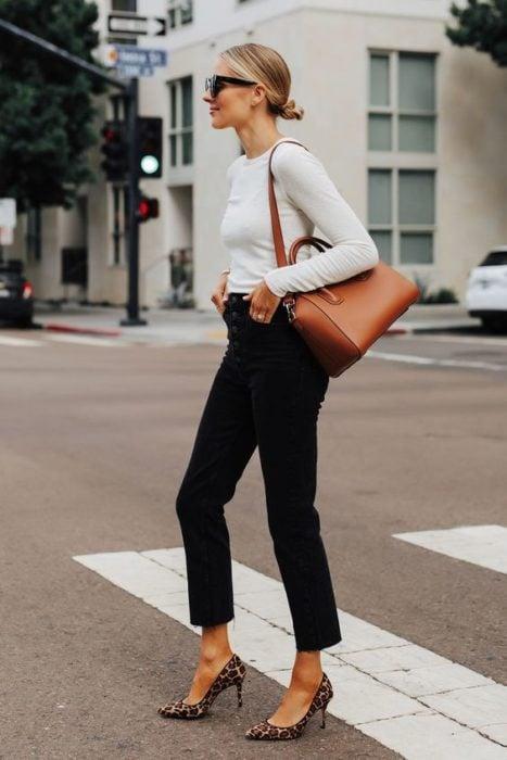 Chica con blusa blanca, pantalón negro y zapatos de animal print