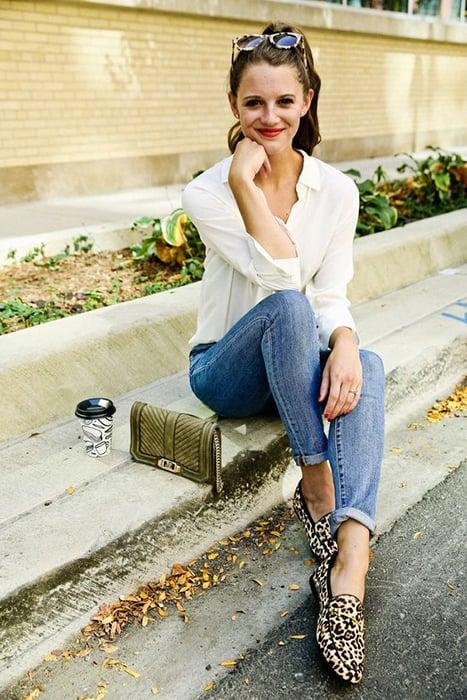 Mujer con blusa blanca, jeans y zapatos animal print sentada en la banqueta con su bolso a un lado