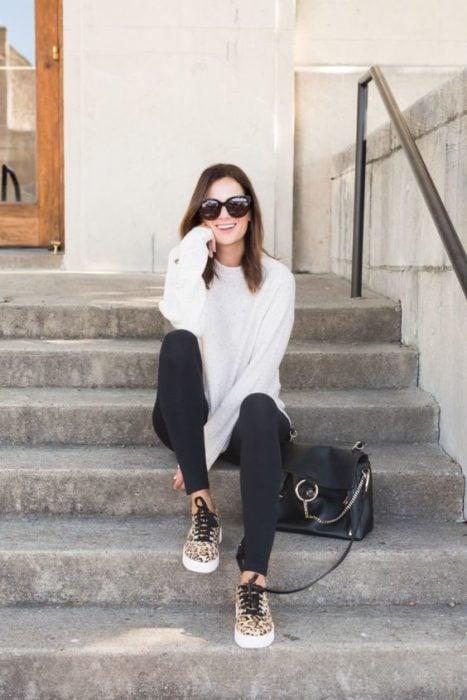 Chica sentada en escalones con sudadera blanca, pantalón negro y tenis animal print