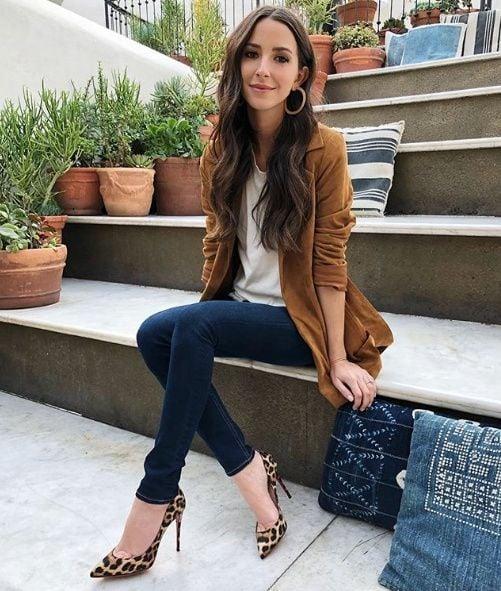 Chica de cabello largo sentada con saco color camel y zapatos animal print