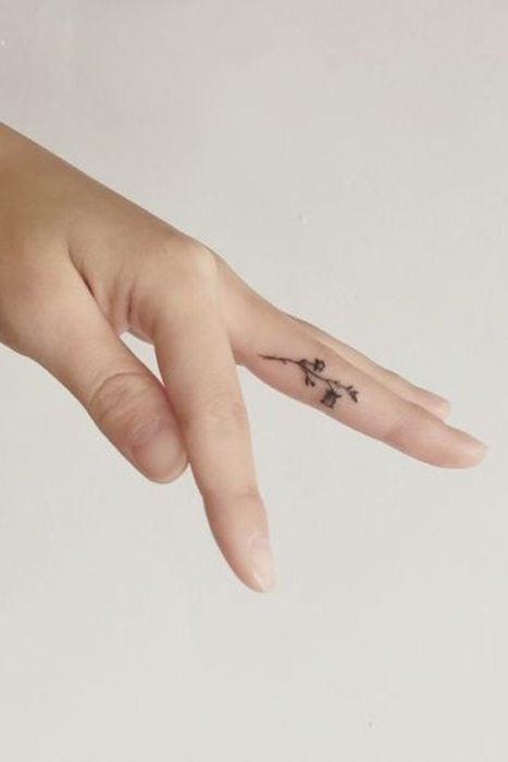 Chica con un tatuaje entre los dedos