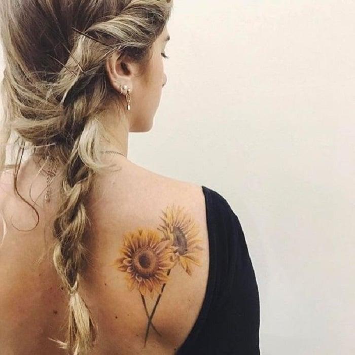 Tatuaje en la zona del hombro de un par de girasoles