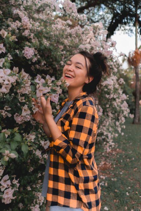 Mujer riendo tocando flores