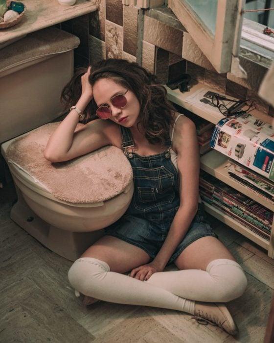 Chica sentada a un lado del inodoro