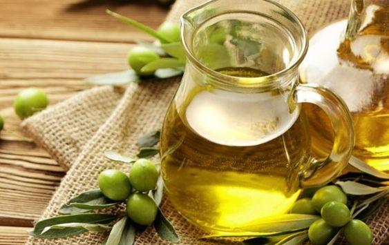 Jarra de cristal con aceite de oliva sobre una tabla de madera