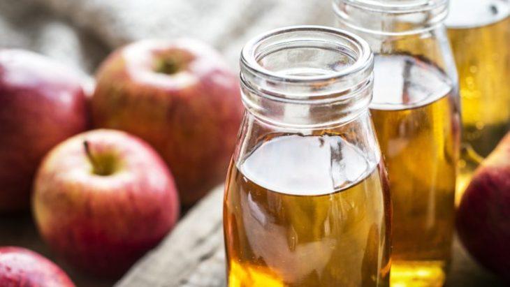 Frasco relleno de vinagre de manza junto a unas manzanas frescas