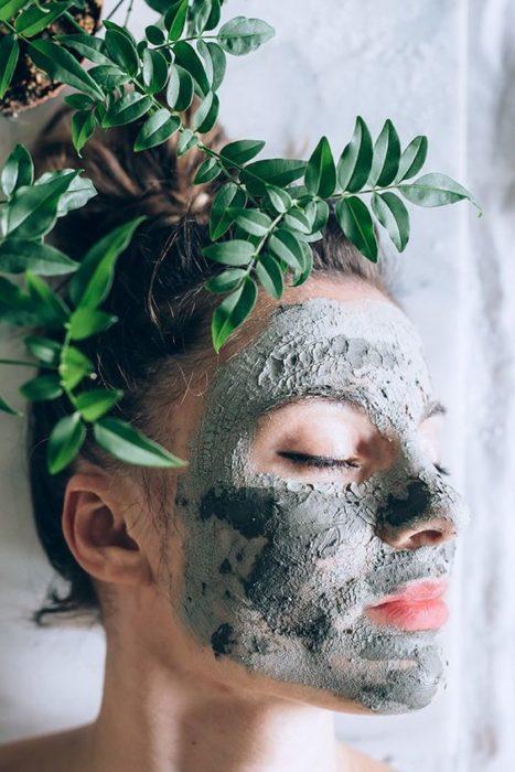 Chica posando de perfil mostrando su rostro con una mascarilla de arcilla verde