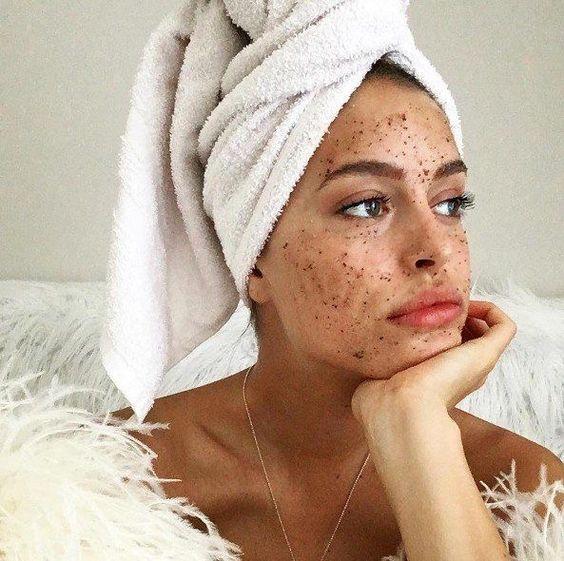 Chica mirando por la ventana, con una toalla enredada en la cabeza y una mascarilla de café molido sobre el rostro