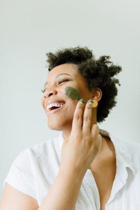 Chica de cabello corto aplicando una mascarilla sobre el rostro