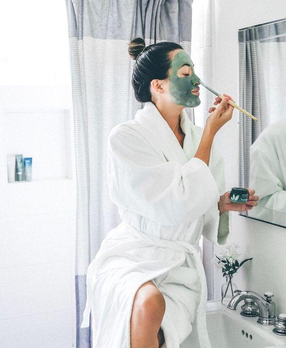 Chica con bata frente al espejo cplicando una mascarilla con brocha
