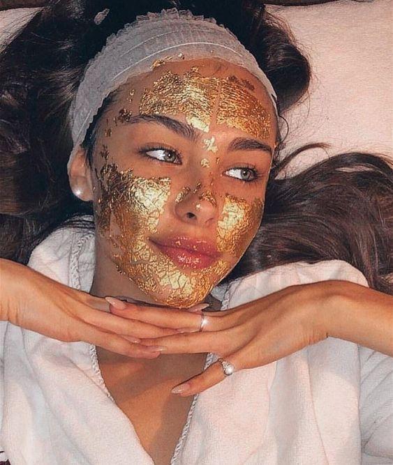 Chica recostada utilizando una mascarilla dorada sobre la piel con las manos cruzadas bajo su barbilla