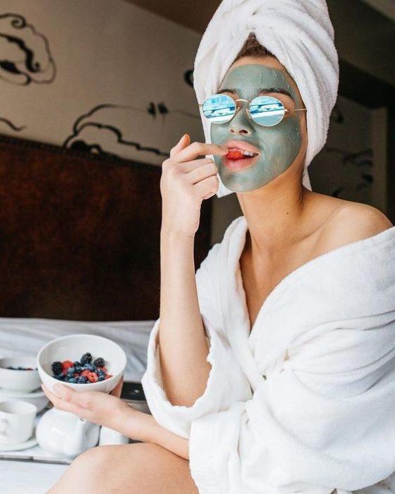 Chica sentada en la orilla de una cama, con una toalla enredada en la cabeza, llevando lentes azules y comiendo frutos rojos