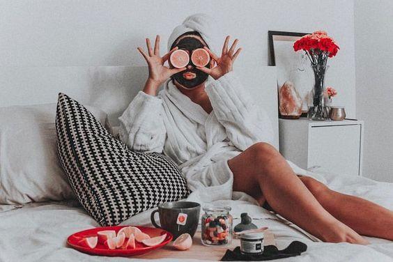 Chica sentada en su cama llevando bata de baño con mascarilla de arcilla negra y rodajas de toronja en el rostro